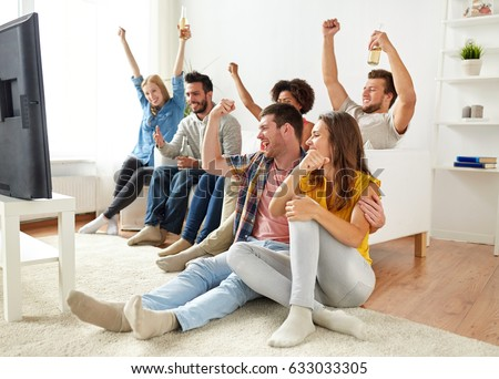friendship, people and entertainment concept - happy friends drinking beer or cider and watching tv at home #633033305
