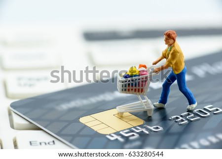 Miniature figurine : a shopper pushes a shopping cart on a smart credit card and a keyboard. Concept of brick and mortar stores nowadays face with increased competition from internet online ecommerce. #633280544