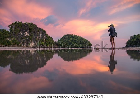 Reflection of Young Asian man photographer taking photo of summer landscape with beautiful sunset sky at Ao Nang Beach. Famous tourist attraction and travel destination of Krabi Province, Thailand