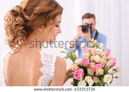 Wedding photographer taking photo of beautiful bride in studio #633313736