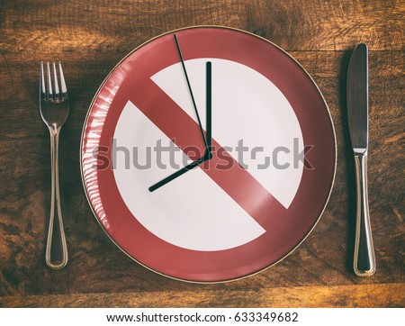 Skip breakfast concept with no symbol and clock on plate Royalty-Free Stock Photo #633349682