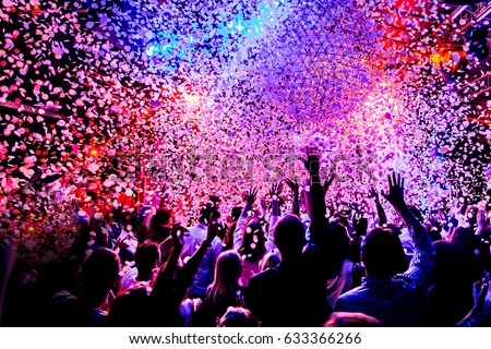 silhouettes of concert crowd in front of bright stage lights and confetti Royalty-Free Stock Photo #633366266
