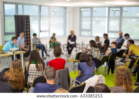 Round table discussion at business and entrepreneurship symposium. Audience in conference hall. Lens focus on unrecognized participant in rear of audience. Royalty-Free Stock Photo #633385253