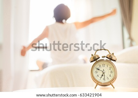 Close up alarm clock with a background of happy woman stretching in bed after wake up in the morning with sunlight from window.