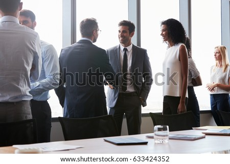 Businesspeople Shaking Hands Before Meeting In Boardroom Royalty-Free Stock Photo #633424352