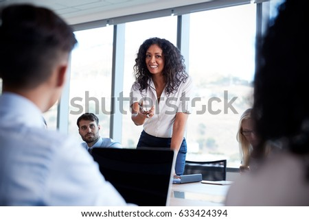 Businesswoman Stands To Address Meeting Around Board Table #633424394