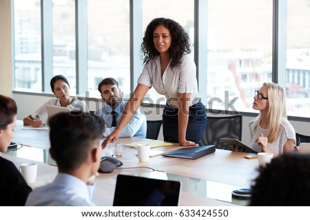 Businesswoman Stands To Address Meeting Around Board Table Royalty-Free Stock Photo #633424550
