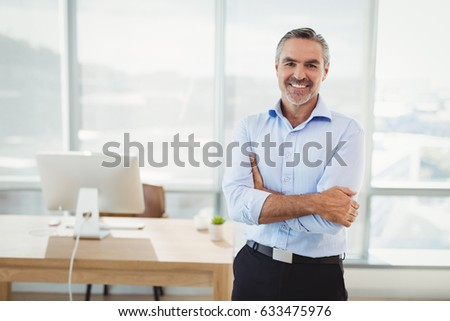 Portrait of smiling executive standing with arms crossed in office #633475976