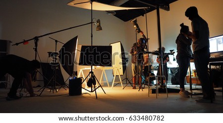 Behind the shooting production crew team and silhouette of camera and equipment in studio. Royalty-Free Stock Photo #633480782