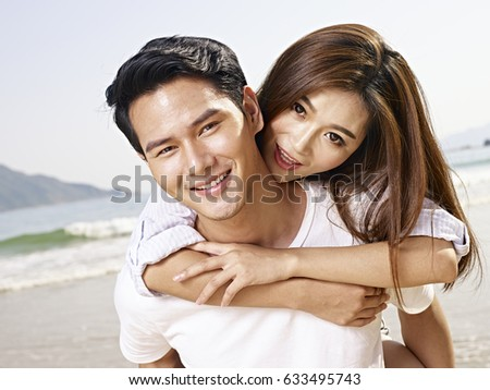 young asian man carrying girlfriend or wife on back on beach. #633495743