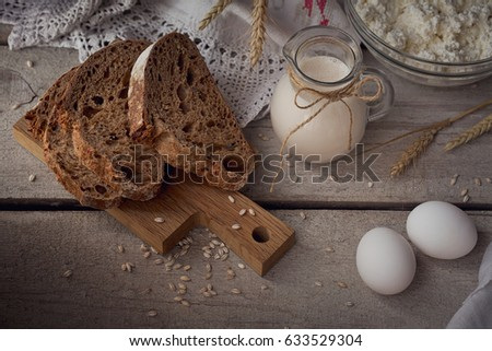 Fresh dairy products. Milk, cottage cheese, sour cream, multigrain homemade bread, fresh eggs and wheat on rustic wooden background. Organic farming dairy concept.  #633529304