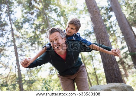 Low angle view of cheerful father piggybacking son in forest #633560108