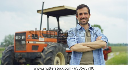 Portrait of a handsome young farmer standing in a shirt and smiling at the camera, on a tractor and nature background. Concept: bio ecology, clean environment, beautiful and healthy people, farmers.  Royalty-Free Stock Photo #633563780