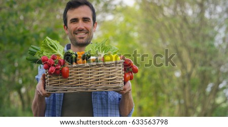 Portrait of a happy young farmer holding fresh vegetables in a basket. On a background of nature The concept of biological, bio products, bio ecology, grown by own hands, vegetarians, salads healthy #633563798