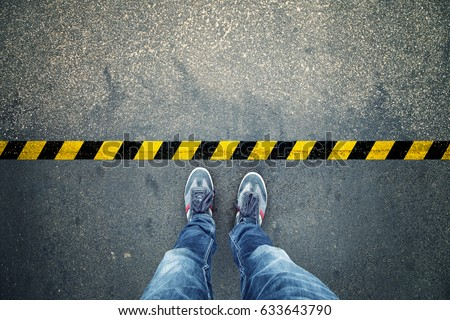 Top view of a man stands on industrial striped asphalt floor with warning yellow black pattern. Royalty-Free Stock Photo #633643790