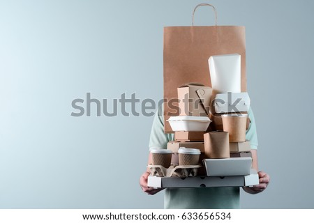 Holding various take-out food containers, pizza box, coffee cups in holder and paper bag, close-up. Light grey background, place to insert your text. Delivery man. #633656534