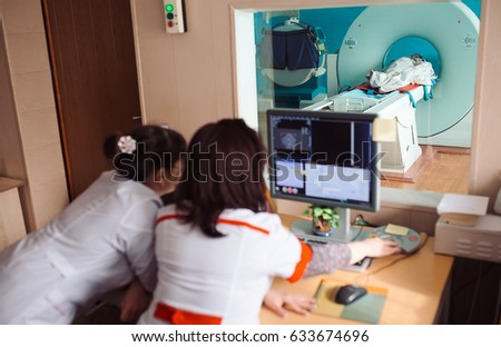 MRI machine and screens with doctor and nurse #633674696