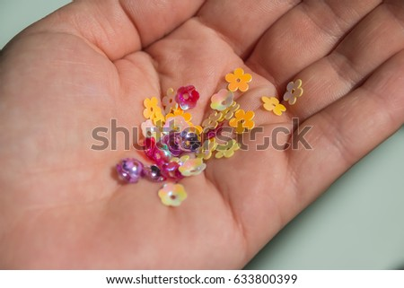 sequins, bead, bugle,marbles in female hands. Multicolored  small beads like a flowers to create hand made jewelry or decorate a clothing #633800399