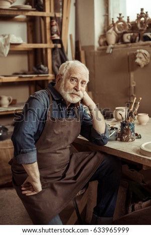 Senior potter in apron sitting at table and looking at camera at manufacturing #633965999