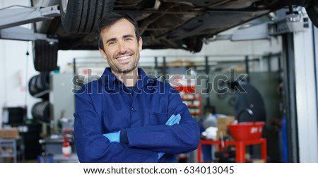 Portrait of a young beautiful car mechanic in a car workshop, in the background of service. Concept: repair of machines, fault diagnosis, repair specialist, technical maintenance and on-board computer Royalty-Free Stock Photo #634013045