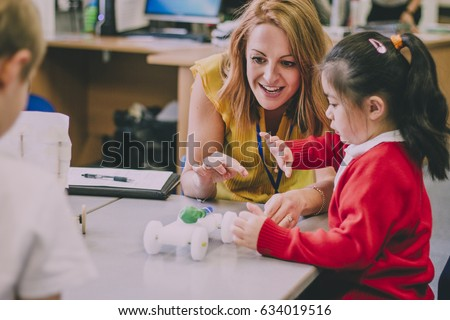 Teacher is sitting at the table in her classroom with her primary school students. They have built a car from recycled objects and crafts equipment and are testing that it works.  Royalty-Free Stock Photo #634019516