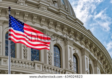 Washington DC Capitol dome detail with waving american flag Royalty-Free Stock Photo #634024823