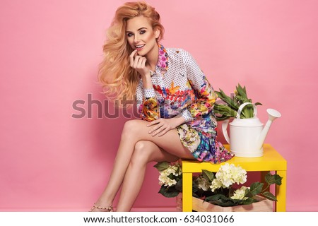 Fashion photo of a beautiful elegant young woman in a pretty dress with flowers and watering can posing over pink background. Fashion photo. Sitting on yellow table. #634031066