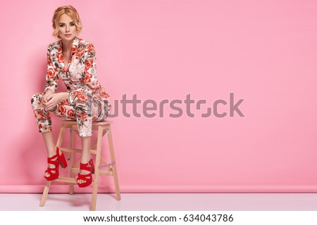 Fashion photo of a beautiful elegant young woman in a pretty suit with flowers holding handbag posing over pink background. Fashion photo #634043786