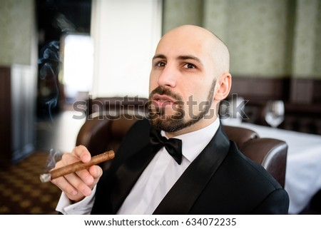 A brutal man in a dress coat smokes a cigar. #634072235