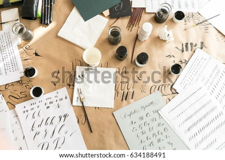 Calligraphy sheets, nibs, paper, ink and pens on a kraft background. Lettering calligraphy workshop. Letters of the English alphabet written with a paint brush. Concept hobby. top view, flat lay. #634188491