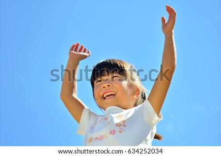 Girls raise hands in the blue sky #634252034