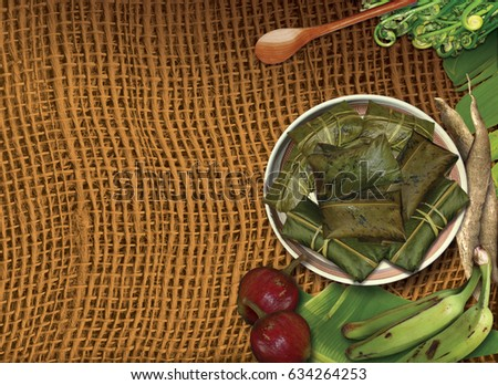 Dish with tamales wrapped in banana leaves on rustic cloth #634264253