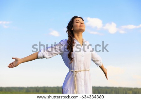 Young happy woman in green field, evening light. Blue sky behind. Royalty-Free Stock Photo #634334360