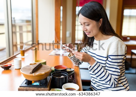 Woman taking photo on her meal in japanese restaurant