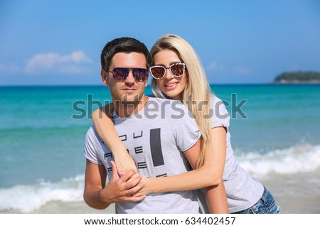 Outdoor closeup portrait of pretty young couple in love having fun in hot weather and feeling happy together on the tropical island. Posing and hugs alone on the beach. #634402457