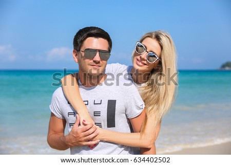 Outdoor closeup portrait of pretty young couple in love having fun in hot weather and feeling happy together on the tropical island. Posing and hugs alone on the beach. #634402502