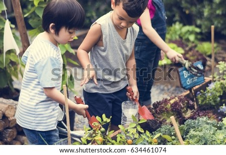 Group of kindergarten kids learning gardening outdoors #634461074