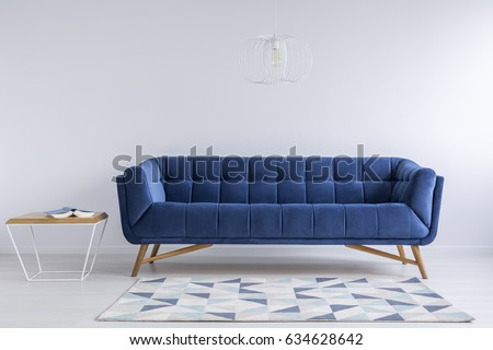 Comfortable blue couch and wooden coffee table in simple white apartment Royalty-Free Stock Photo #634628642