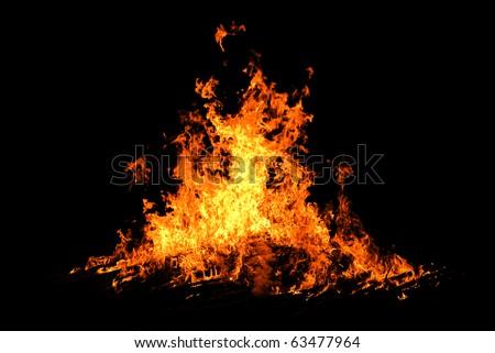 Night bonfire orange hot flames on black background in the night #63477964