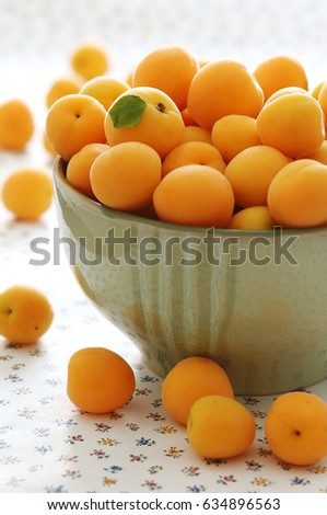fresh apricots in a big green bowl, close up, day light, selective focus #634896563