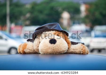Dog stuffed animal on car roof