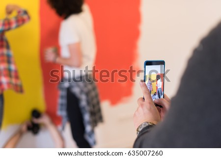 happy smiling young couple painting interior wall of new house #635007260
