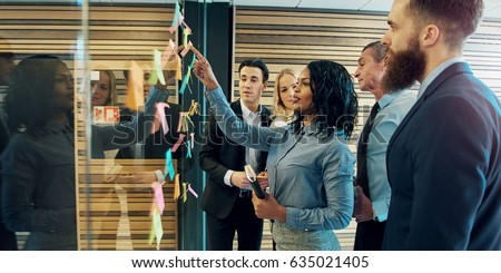 Creative group of business people brainstorming putting sticky notes on glass wall in office Royalty-Free Stock Photo #635021405