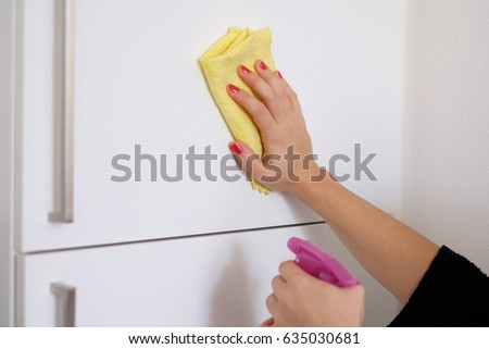 Woman cleaning white surface in  the kitchen at home #635030681