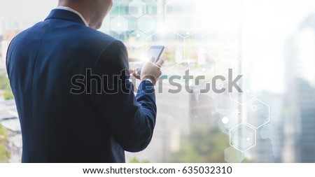 Business man using smart phone on window with futuristic technology connection shape over the network connection background #635032310