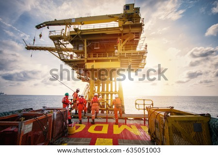 Offshore oil and gas platform during crew boat transfer worker to the platform during sunset time #635051003