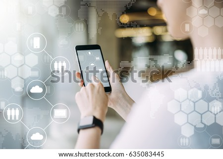 Close-up of smartphone in female hands.In foreground are virtual icons with picture of clouds,people and digital gadgets.Social media.Girl blogging,chatting online.Cloud technology.Blurred background.