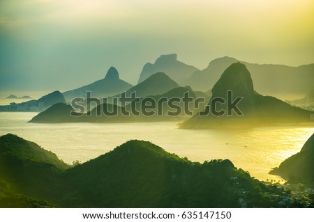 Scenic summer sunset view of the dramatic landscape setting of Rio de Janeiro, Brazil with mountain silhouettes towering over Guanabara Bay #635147150