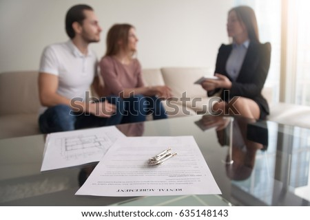 Young renters couple sitting on couch discussing renting apartment with real estate agent, focus on rental agreement and keys, property lease contract. Looking for accommodation, long-term tenancy Royalty-Free Stock Photo #635148143