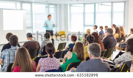 Business and entrepreneurship symposium. Speaker giving a talk at business meeting. Audience in conference hall. Rear view of unrecognized participant in audience. #635182898